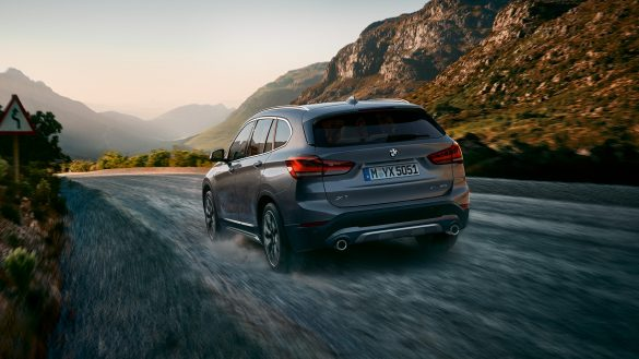 BMW X1 von rechts hinten mit hügeliger Landschaft