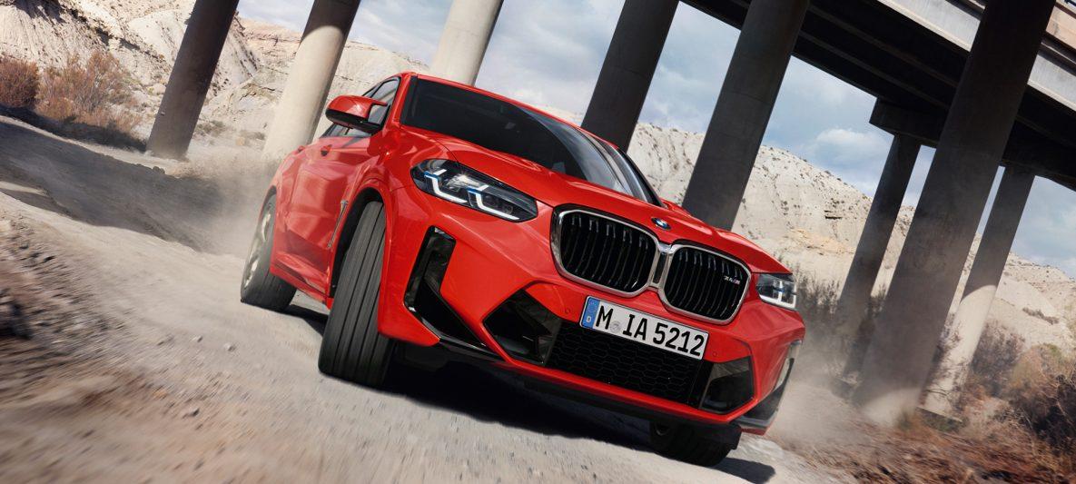 BMW X4 M F98 LCI Facelift 2021 Toronto Rot metallic Dreiviertel-Frontansicht vor Brückensäulen