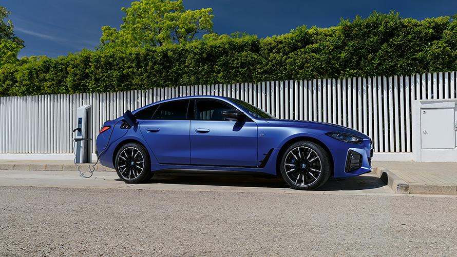 BMW i4 M50 G26 2021 BMW Individual Frozen Portimao Blau metallic Seitenansicht angeschlossen an Ladesäule